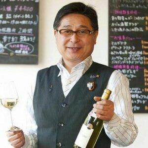ワインのボトルとグラスを持つ店主・松岡修司